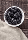 Blackberry dans la cuvette blanche sur le conseil en bois grunge Images libres de droits