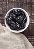 Blackberry in der weißen Schüssel auf hölzernem Brett des Schmutzes Lizenzfreie Stockbilder