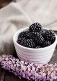 Blackberry in der weißen Schüssel und in den Blumen auf hölzernem Hintergrund Stockfotografie