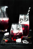 Blackberry drink in glasses with black sugar rim for fall and halloween parties. Royalty Free Stock Images