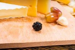 Blackberry en el tablero de madera con la variedad de quesos Foto de archivo libre de regalías