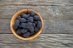 Blackberry fruit in  bamboo bowl on wooden background Stock Images
