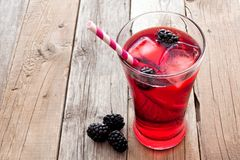 Blackberry fruit drink with straw over rustic wooden background. Blackberry fruit drink in a glass with straw over a rustic wooden background Stock Photography