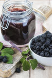 Blackberry jam. A pot with blackberry jam and some fresh fruits and leaves Stock Photo