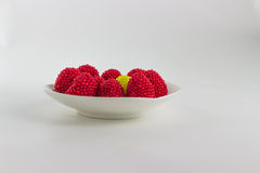 Blackberry jelly red, green, yellow and blue. On a white saucer, white background Stock Photos
