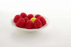 Blackberry jelly red, green, yellow and blue. On a white saucer, white background Royalty Free Stock Photo