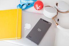 BlackBerry Leap smartphone, Apple MacBook and accessorizes. Moscow, Russia - May 25, 2015: BlackBerry Leap back, Apple MacBook Pro Retina, Parrot Zik ear-flaps Royalty Free Stock Images