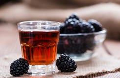 Blackberry likör i ett skottexponeringsglas Arkivbilder