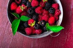 Blackberry och hallonet i en metall bowlar på röd träbakgrund Top beskådar Royaltyfri Foto