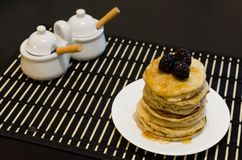 Blackberry pancakes with maple syrup containers Royalty Free Stock Photography