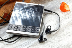BlackBerry Passport on wooden table Royalty Free Stock Photos