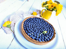 Blackberry pie with whipped cream and flowers on rustic background, top view, unique perspective. Morning and breakfast. Concept stock photo