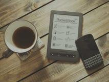 Blackberry Qwerty Phone Near Gray Pocket Book Case Beside Black Rim White Ceramic Teacup Royalty Free Stock Photo