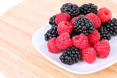 Blackberry and raspberries on white plate Stock Photos