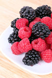 Blackberry and raspberries on white plate. Closeup Stock Photography