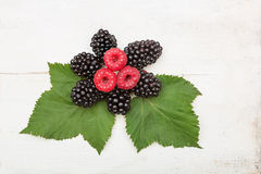Blackberry and raspberry with green leaves on wooden background. Blackberry and raspberry with green leaves on light wooden background Stock Photos