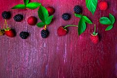 Blackberry and raspberry on red wooden background. Top view. Frame. Flat lay.  Royalty Free Stock Photos