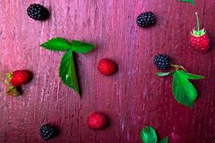 Blackberry and raspberry on red wooden background. Top view. Frame. Flat lay.  Royalty Free Stock Photo