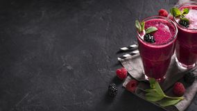 Blackberry and raspberry smoothies in glass with mint leaf and r. Aw beeries on black background Stock Photography