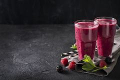 Blackberry and raspberry smoothies in glass with mint leaf and r. Aw beeries on black background Stock Image
