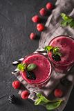 Blackberry and raspberry smoothies in glass with mint leaf and r. Aw beeries on black background Stock Photos