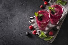 Blackberry and raspberry smoothies in glass with mint leaf and r. Aw beeries on black background Royalty Free Stock Photo