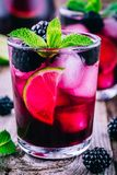 Blackberry smash cocktail with lime, and mint. Blackberry smash cocktail with lime, mint and ice royalty free stock image