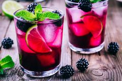 Blackberry smash cocktail with lime, and mint. Blackberry smash cocktail with lime, mint and ice royalty free stock photography