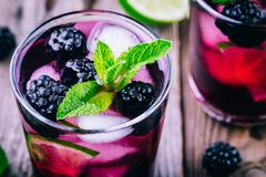 Blackberry smash cold cocktail  with lime, and mint. Blackberry smash cold cocktail  with lime,  mint and ice Royalty Free Stock Photo