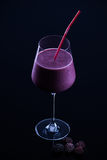 Blackberry smoothie. Glass of blackberry smoothie with a straw Royalty Free Stock Photo