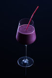 Blackberry smoothie. Glass of blackberry smoothie with a straw stock image