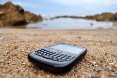 Blackberry telefon på stranden royaltyfria bilder