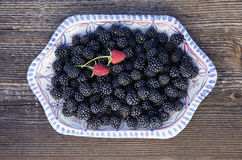 Blackberry and two red raspberry in ceramic plate. Fresh ripe blackberry and two red raspberry in ceramic plate Stock Photo