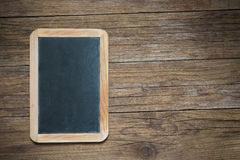 Blackboard on antique wooden table Royalty Free Stock Image