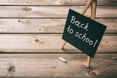 Blackboard with back to school text, dark wooden background, copy space stock photo