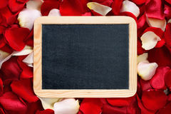 Blackboard on background of rose petals Royalty Free Stock Photo