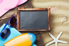 Blackboard and beach gear lie on the sand Royalty Free Stock Image