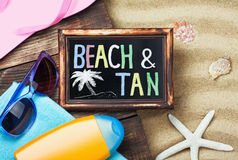 Blackboard and beach gear lie on the sand Royalty Free Stock Photography