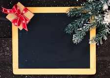 Blackboard blank with christmas decoration. Blackboard decorated with fir branch and a gift box Royalty Free Stock Image