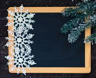 Blackboard blank with christmas decoration. Blackboard blank decorated with fir branch and snowflakes Stock Image