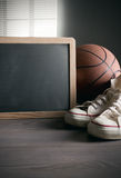 Blackboard with canvas shoes and basketball Royalty Free Stock Photography