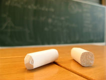 Blackboard and chalk. Two pieces of chalk in the foreground on a table and quantum mechanics scribble on the blackboard behind royalty free stock photo