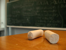 Blackboard and chalk. Two pieces of chalk in the foreground on a table and quantum mechanics scribble on the blackboard behind stock images