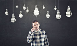 Blackboard with chalk drawing of lightbulb overhead. Stock Photography