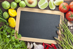 Blackboard Chalkboard Vegetables Sign Background. Various fresh vegetables and herbs around the edge of a blank chalkboard sign on a wood table Royalty Free Stock Image