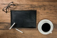 Blackboard with chalks for design inspiration. Cup of coffee on a wooden desk background and a blank blackboard with two white chalks for design inspiration for Royalty Free Stock Image