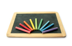 Blackboard and chalks in rainbow Stock Images