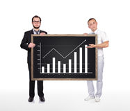 Blackboard  with chart. Two businessman holding blackboard  with drawing chart Royalty Free Stock Photos