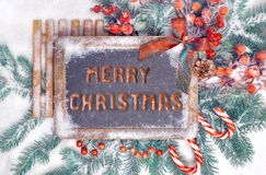 Blackboard with greeting text in English and Christmas decoratio. Blackboard with Christmas decorations on snow, greeting `Merry Christmas` written with biscuits Stock Photos