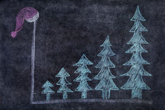 Blackboard with Christmas trees and santa hat Royalty Free Stock Photography